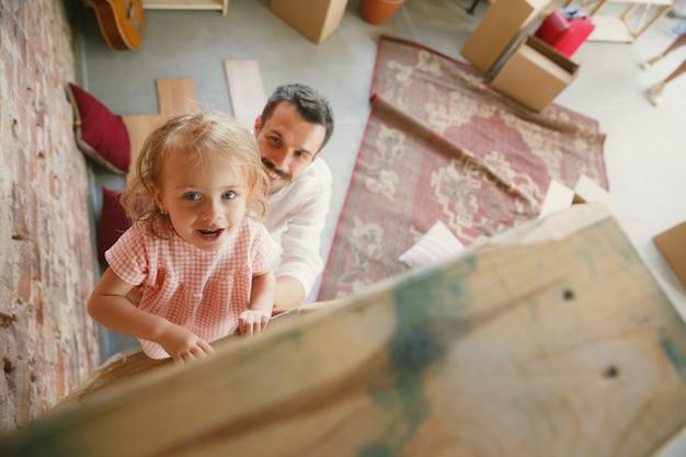 Vida nova. o jovem pai e a filha mudaram-se para uma nova casa ou apartamento. pareça feliz e confiante. movimento, relações, conceito de estilo de vida. brincando juntos, preparando-se para consertar e rindo.