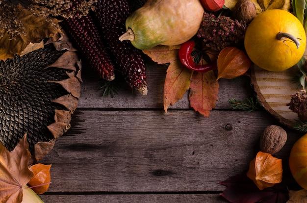 Vida rural temperamental escura ainda com abóboras laranja brilhantes, girassol, physalis e folhas de outono coloridas. composição outonal em uma superfície de madeira velha.