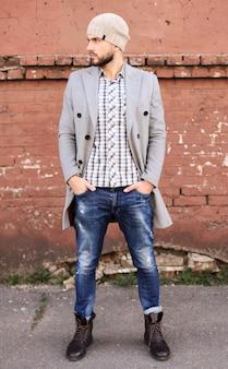Vida urbana. jovem elegante de casaco cinza e chapéu em pé na rua da cidade.