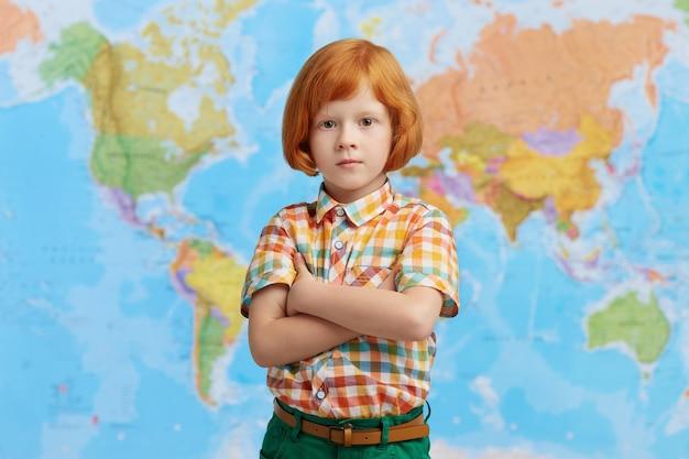 Vidente menino pequeno com cabelos ruivos, mantendo as mãos cruzadas em pé contra o mapa, vindo para o professor de geografia. clver garoto vai para a primeira classe, tendo um olhar confiante