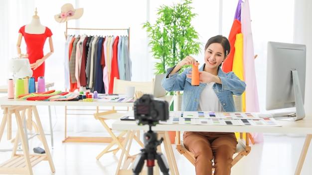 Vídeo ao vivo de jovens lindos designers de moda asiáticos mostrando novo material com a rede online de consumidores. ela vende seu produto para pessoas em todo o mundo. desfocada em primeiro plano.