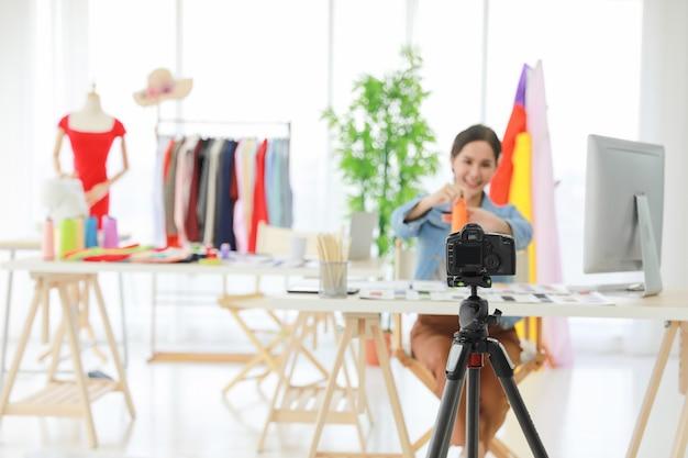 Vídeo ao vivo de jovens lindos designers de moda asiáticos mostrando novo material com a rede online de consumidores. ela vende seu produto para pessoas em todo o mundo.
