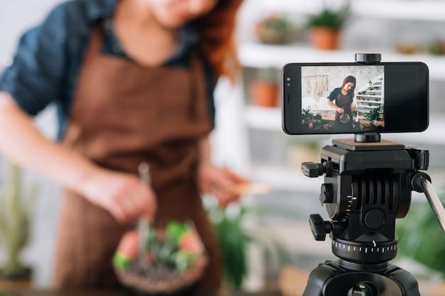 Vídeo blog de florista. foto recortada de mulher usando a câmera do smartphone para transmitir o tutorial online de jardinagem doméstica.