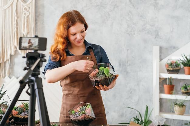 Vídeo blog de florista. mulher usando a câmera do smartphone para transmitir um tutorial online de jardinagem doméstica, plantando suculentas.