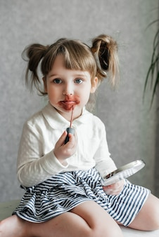 Vídeo-blogueira de bebê fofa caucasiana, telefone em um tripé