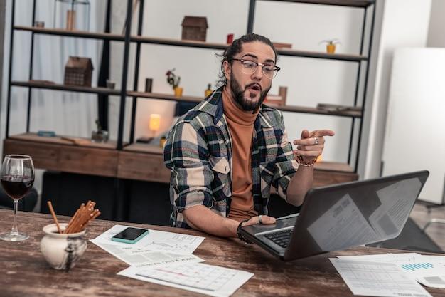Video chamada. homem alegre e positivo apontando para a tela do laptop enquanto faz uma videochamada