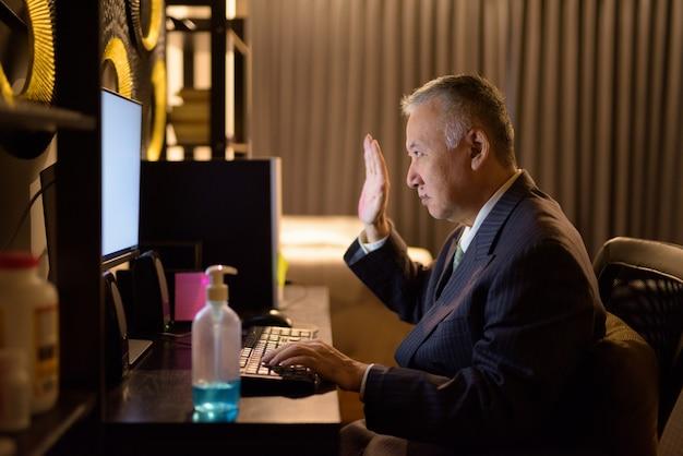 Vídeo chamada japonesa madura do homem de negócios ao trabalhar horas extras em casa tarde da noite