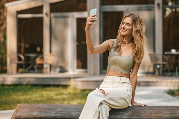 Video chamada. mulher jovem e bonita sorrindo regozijando-se sentada ao ar livre olhando para o smartphone com a mão estendida em um dia bom