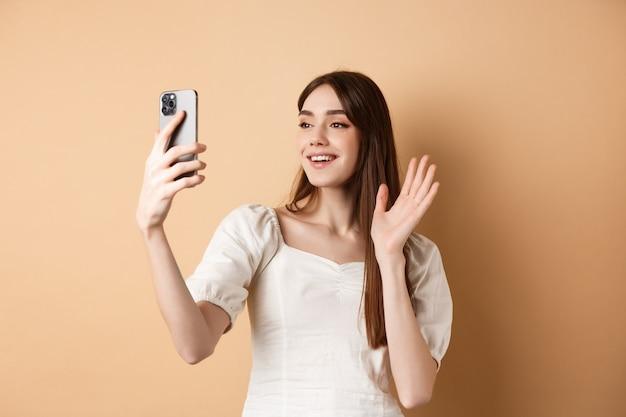 Vídeo chat de garota no telefone, dispensando a mão na câmera do celular e dizendo olá, conversando com um amigo, sorrindo e de pé sobre um fundo bege.
