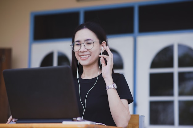 Vídeo-conferência de mulheres asiáticas pelo notebook computador, novo distanciamento de chamada de vídeo normal social