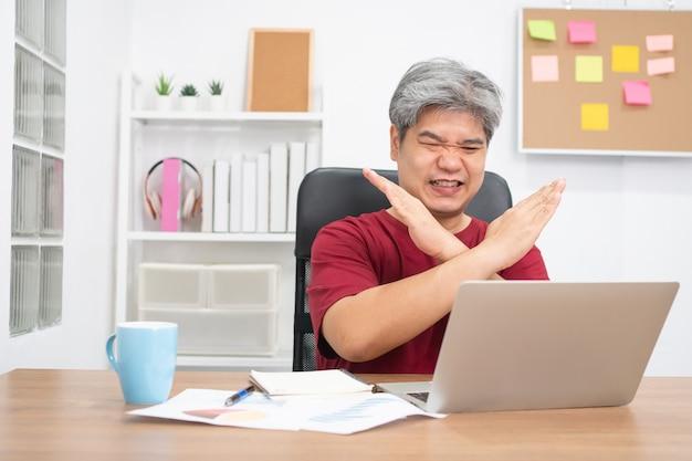 Vídeo-conferência do empresário asiático que chama o laptop para uma educação de aprendizagem on-line em casa.