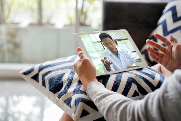 Vídeo-conferência do homem para consulta com médico especialista em casa para telemedicina