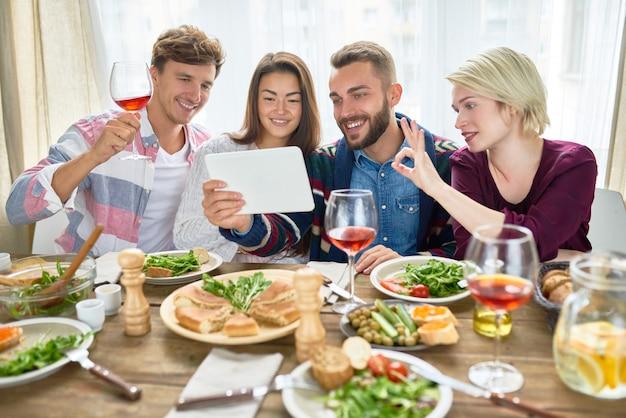 Vídeo de amigos felizes chamando na mesa de jantar