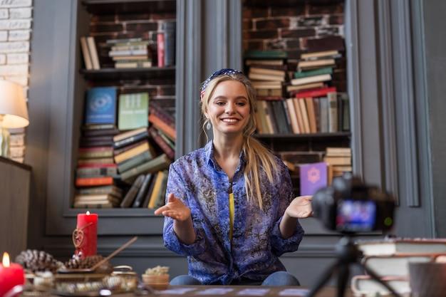Vídeo especial. mulher alegre e positiva sorrindo para a câmera enquanto grava um vídeo sobre leitura da sorte Foto Premium