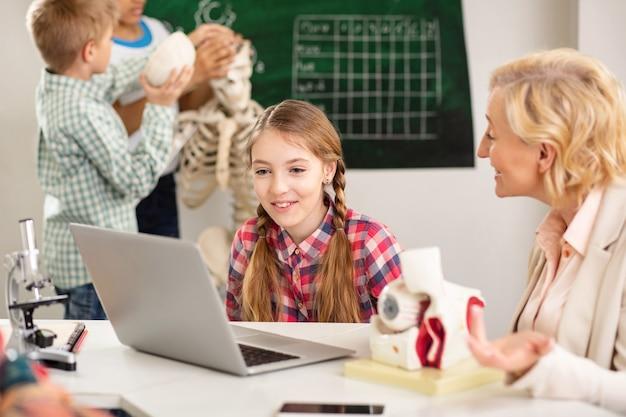 Vídeo interessante. garota legal e feliz olhando para a tela do laptop enquanto assiste a um documentário