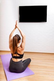 Vídeo na tela do laptop com exercícios de ioga em casa.