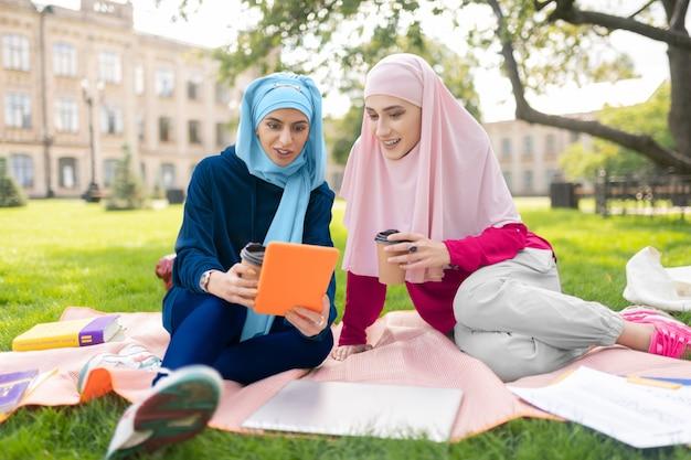 Vídeo no tablet. alunos muçulmanos assistindo a um vídeo no tablet e bebendo café enquanto estão sentados no gramado