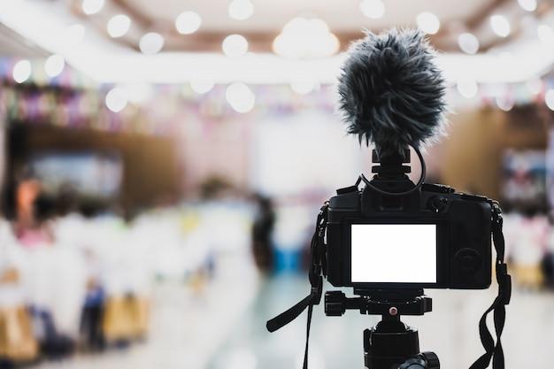 Vídeo ou espelho digital profissional em tripé para gravação de câmera com microfone tirando foto no salão de convenções de casamento em evento de transmissão ao vivo, equipamento de produção de seminários.