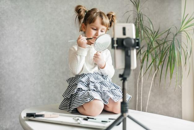Vídeo vlogger de bebê fofo, caucasiano, telefone em um tripé.