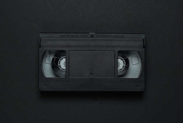 Videocassete em um fundo preto. mídia de armazenamento retrô, videoteipe. anos 80