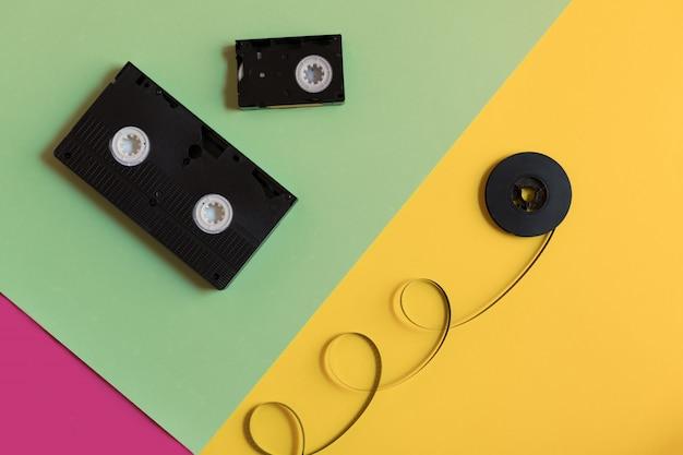 Videocassete retro e filme em um fundo de papel pastel de três cores.