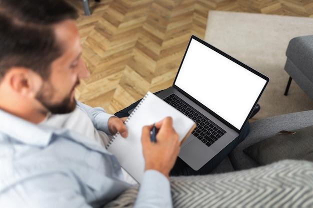 Videochamada, conceito de reunião de negócios online. freelancer caucasiano usa computador portátil para reunião online, olhando para a tela vazia da maquete, sentado no sofá. educação a distância, aprendizagem online