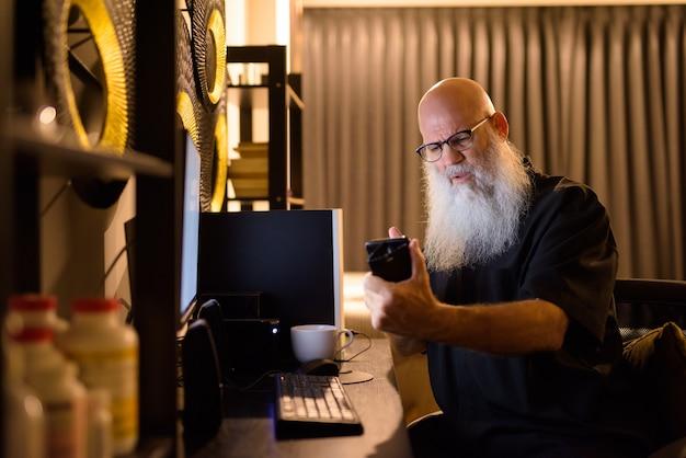 Videochamada de homem maduro de barba careca estressado enquanto trabalhava horas extras em casa tarde da noite