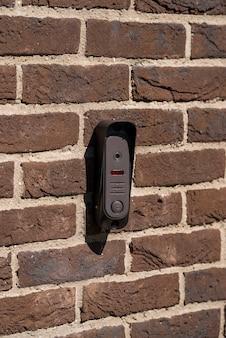 Videochamada de rua para qualquer clima na parede de tijolos na entrada