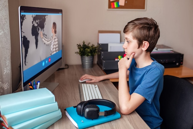 Videoconferências de menino com um tutor no computador em casa do ensino a distância