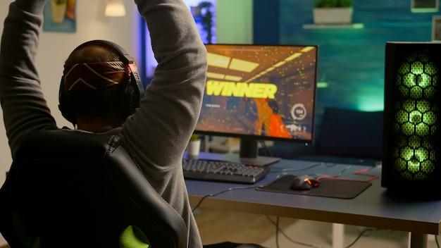 Videogamer jogando gráficos no espaço cibernético sentado na cadeira de jogos usando tecnologia de rede sem fio. homem fazendo streaming de videogames online para se divertir usando equipamentos rgb para campeonatos online
