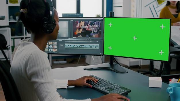 Videógrafa africana com fone de ouvido processando montagem de filme