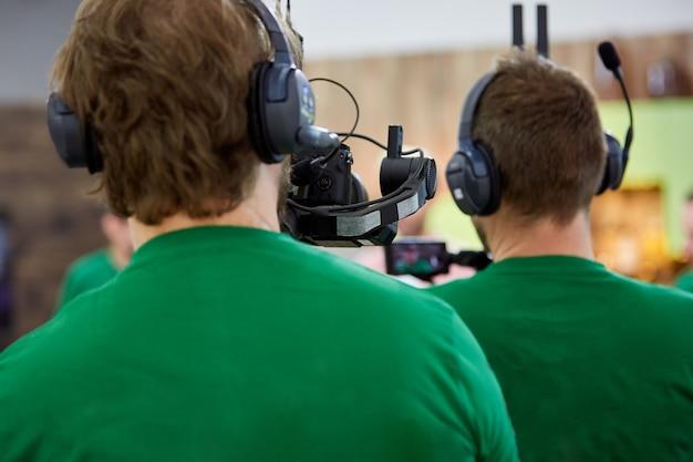 Videógrafo fazendo um filme ou programa de televisão com uma câmera profissional, nos bastidores.
