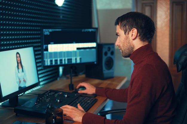 Videógrafo masculino edita e corta filmagens e sons em seu computador pessoal