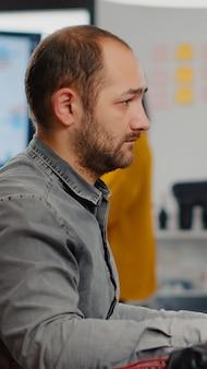 Videógrafo olhando para a câmera sorrindo trabalhando no local de trabalho de inicialização criativa