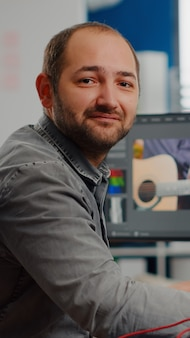 Videógrafo sorrindo para a câmera trabalhando no computador, editando imagens de vídeo e aplicativo de áudio sentado no mo ...