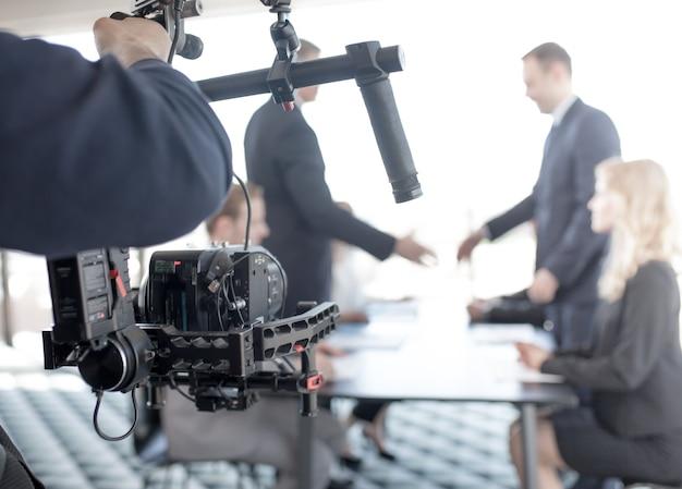 Videógrafo usando steadycam, fazendo vídeo de empresários apertando as mãos