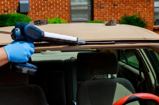 Vidraceiro usando ferramentas de silicone, reparando o para-brisa em uma substituição de pára-brisa de automóvel
