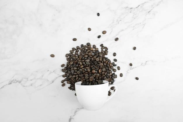 Vidro branco virado e grãos de café dispostos em uma superfície de mármore na vista superior.