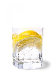 Vidro com água com gás e rodelas de limão no fundo branco