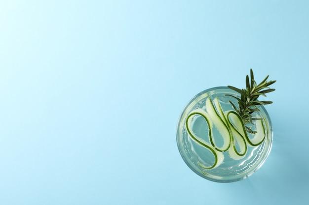 Vidro com água de pepino na superfície azul