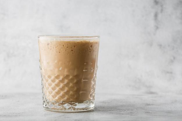Vidro com café frio e leite isolado no fundo de mármore brilhante. visão aérea, copie o espaço. publicidade para o menu de café. menu de café. foto horizontal.