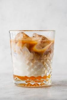 Vidro com café frio e leite isolado no fundo de mármore brilhante. visão aérea, copie o espaço. publicidade para o menu de café. menu de café. foto vertical.