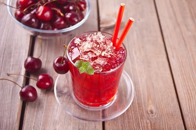 Vidro com chá gelado doce caseiro de cereja fresca ou coquetel, limonada com hortelã. bebida refrescante e fria. festa de verão.