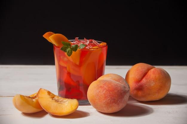 Vidro com chá gelado doce fresco do pêssego caseiro ou cocktail, limonada com hortelã.