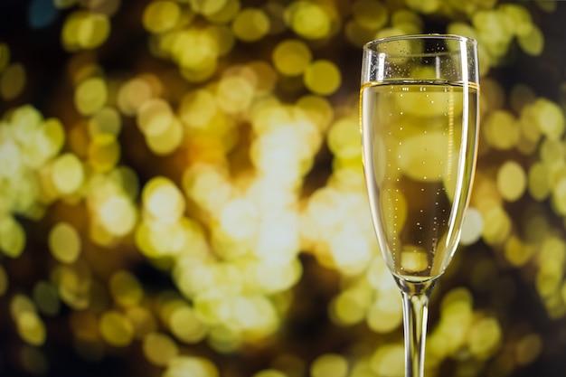 Vidro com champanhe em luzes de bokeh