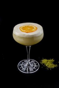 Vidro com cocktail cremoso com fatia de creme e laranja e wasabi em fundo preto