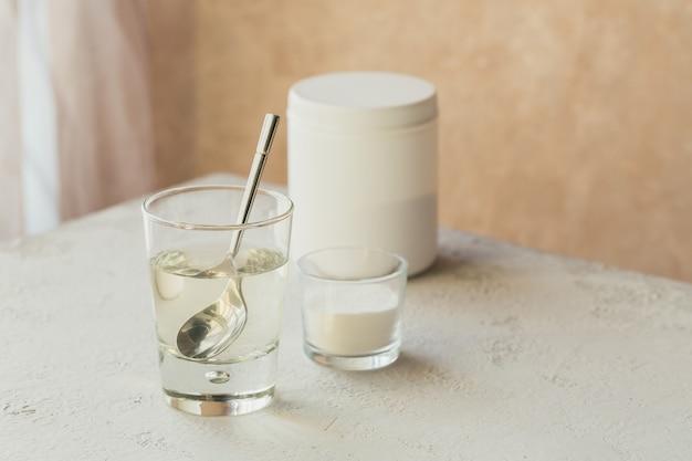 Vidro com colágeno dissolvido em água e pó de proteína de colágeno na mesa bege claro. conceito de estilo de vida saudável.