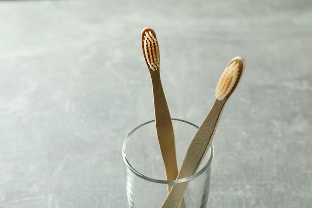 Vidro com escovas de dentes ecológicas em fundo cinza