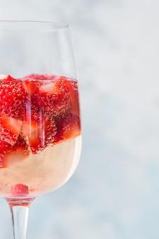 Vidro com gelo verão caseiro sangria vermelha fria coquetel com morango em vidro na parede azul. conceito de férias, verão