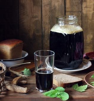 Vidro com kvass de centeio, folhas de hortelã e groselha preta em cima da mesa.